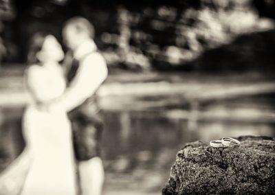 Anillos de boda con novios de fondo